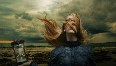 Девушка с волосами на лице держит песочные часы