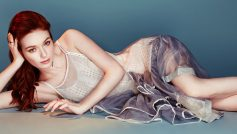 Английская актриса Элеонор Томлинсон лежит в платье на сером фоне